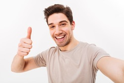 Photo of handsome man in casual t-shirt and bristle on face smiling on camera with thumb up while taking selfie isolated over white background