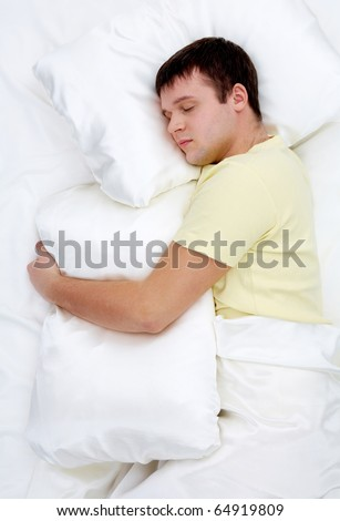 Photo of handsome man sleeping and holding soft white pillow