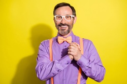 Photo of handsome mature man happy positive smile hold hands together formalwear isolated over yellow color background