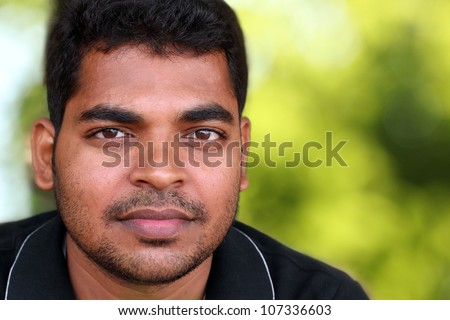 Photo of handsome middle-aged Indian/asian youth with content and satisfied look. The eyebrows are thick and prominent and hair is black and curly with unshaven stubble on the face.