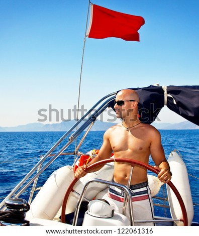 Photo of handsome muscular man at the helm of ship, sailing at Mediterranean sea, traveling the world by sailboat, male model on luxury yacht, water sport vacation, summer outdoors - stock photo