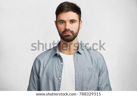 Photo of handsome serious bearded man with thick black mustache and beard wears shirt, looks confidently into camera, has serious expression as listens important information isolated on white #788329315