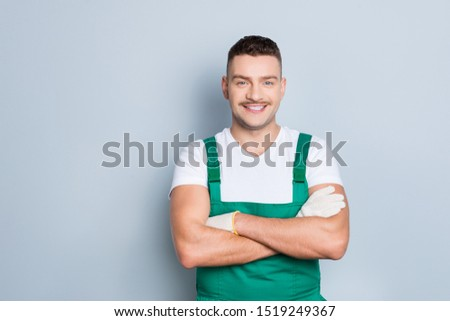 Photo of handsome virile muscles guy holding arms crossed self-confident best manual worker skilled engineer wear green safety dungarees isolated grey background