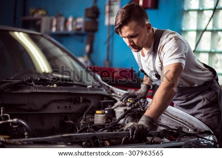 Photo of handsome worker of service station repairing vehicle #307963565