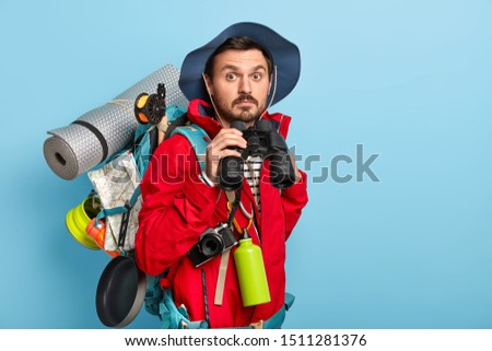 Photo of handsome young male tourist holds binoculars, walks in forest, wears casual clothes, carries necessary things for traveling, likes to spend holidays in active wear. Adventure, travel concept