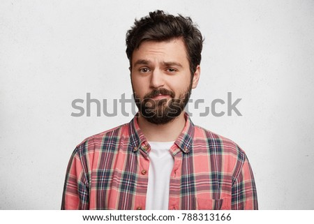 Photo of handsome young man with trendy hairdo and mustache, curves lips and frowns face in bewildermennt, isolated over white concrete background. Attractive male student in casual clothes. #788313166