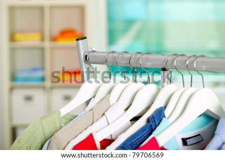 Photo of hangers with different clothes in department