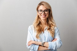 Photo of happy blond businesswoman wearing eyeglasses smiling and standing with hands crossed isolated over gray background