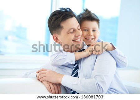 Photo of happy boy embracing his dad and looking at camera