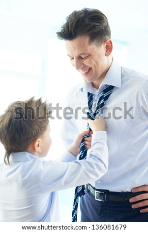 Photo of happy boy helping his father tie necktie