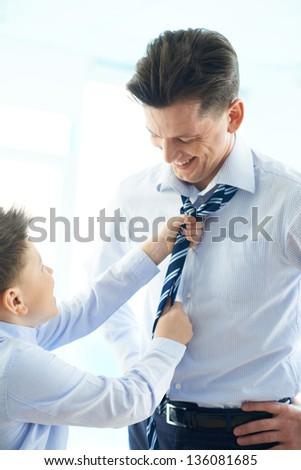 Photo of happy boy helping his father tie necktie