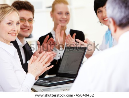Photo of happy business partners applauding to their senior leader after making report