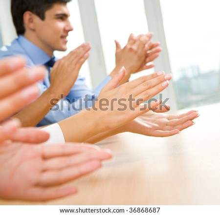 Photo of happy business partners hands applauding at meeting