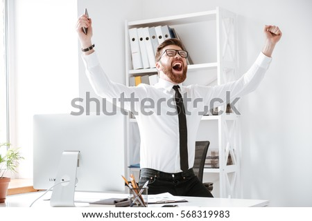 Photo of happy businessman standing in office near computer make winner gesture.
