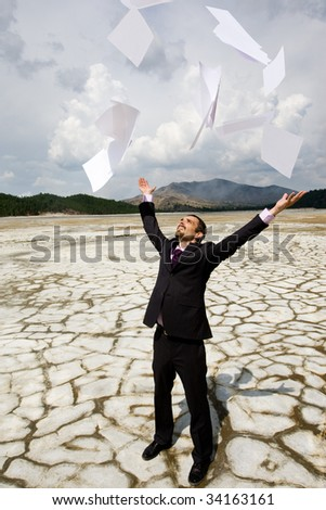 Photo of happy businessman standing on dry ground and throwing papers upwards
