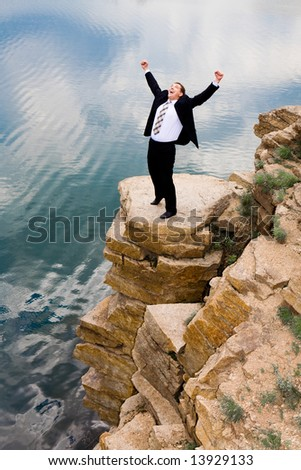 Photo of happy businessman standing on the mountain and raising his hands