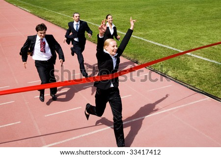 Photo of happy businesswoman crossing finish line during race