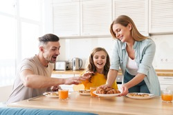 Photo of happy caucasian beautiful family smiling and eating croissants while having breakfast in modern kitchen