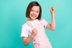 Photo of happy charming nice little girl winner raise fists smile isolated on pastel teal color background