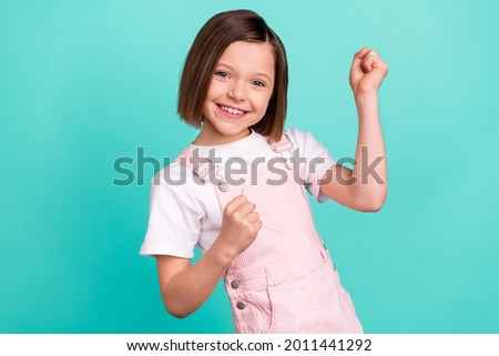 Photo of happy charming nice little girl winner raise fists smile isolated on pastel teal color background 商業照片 ©