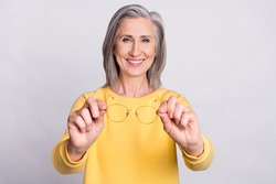 Photo of happy cheerful beautiful smiling mature woman give you glasses bad eyesight isolated on grey color background
