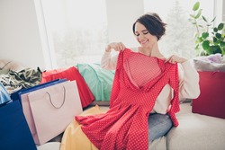 Photo of happy cheerful lady try on dress sit sofa sale bags nice purchase indoors inside home living room