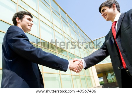 Photo of happy co-workers handshaking outdoors at background of modern building