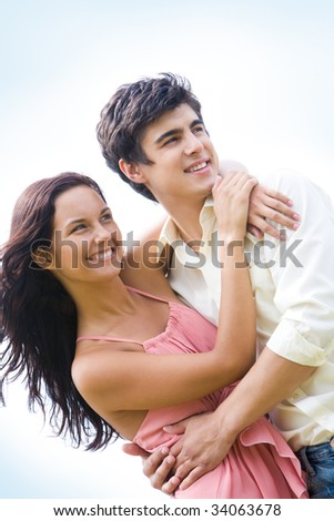 Photo of happy couple embracing each other and looking aside