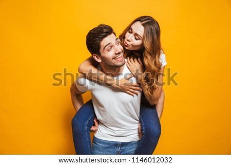 Photo of happy couple having fun while man carrying beautiful woman on his back isolated over yellow background