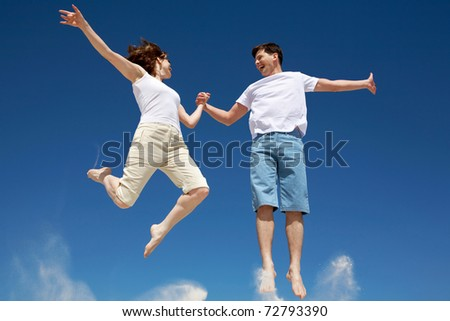 Photo of happy couple in jump with bright blue sky at background