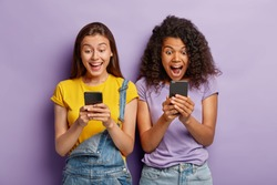 Photo of happy diverse female friends ignore live communication, chat in web blog via cell phones, gaze with positive expressions at screens, wear casual clothes, stand shoulder to shoulder.