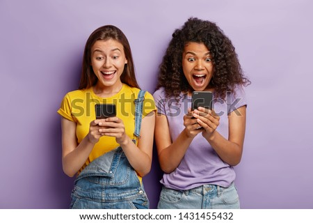Photo of happy diverse female friends ignore live communication, chat in web blog via cell phones, gaze with positive expressions at screens, wear casual clothes, stand shoulder to shoulder. #1431455432
