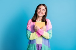 Photo of happy dreamy young woman look empty space hold favourite book isolated on blue color background
