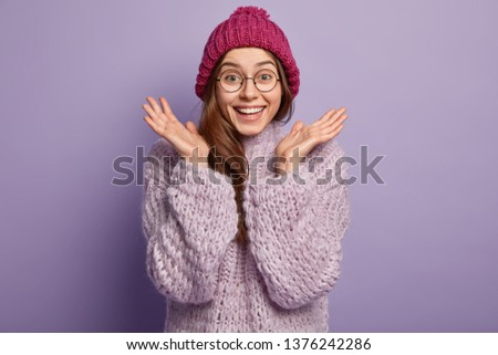 Photo of happy emotive European woman gestures with both hands, clasps palms, wears round spectacles, dressed in winter hat, knitted jumper, isolated over purple background. Good emotions concept #1376242286