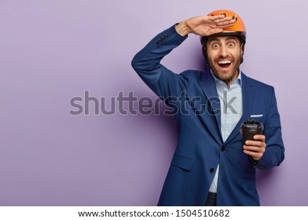 Photo of happy European guy keeps palm near forehead, drinks takeout coffee, wears headgear and formal suit, tries to see something into distance, poses over purple studio wall. Construction worker
