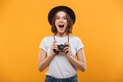Photo of happy excited emotional young woman photographer tourist standing isolated over yellow background holding camera.