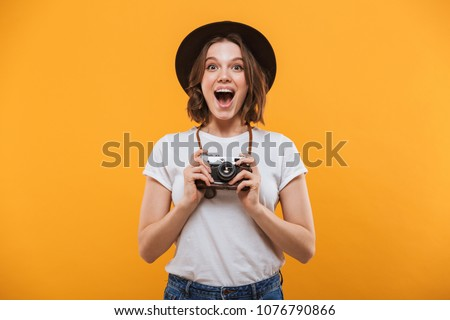 Photo of happy excited emotional young woman photographer tourist standing isolated over yellow background holding camera. #1076790866