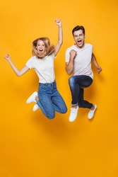 Photo of happy excited young loving couple jumping isolated over yellow wall background.
