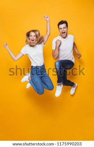 Photo of happy excited young loving couple jumping isolated over yellow wall background. #1175990203