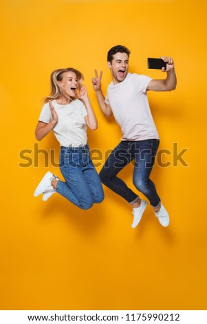 Photo of happy excited young loving couple jumping isolated over yellow wall background make a selfie.