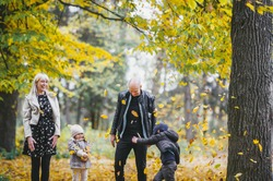 Photo of happy family in autumn park, parents with cheerful babies playing in fall forest, mother and father with daughter and son having fun in autumnal woods. Happiness concept, pleasure time.