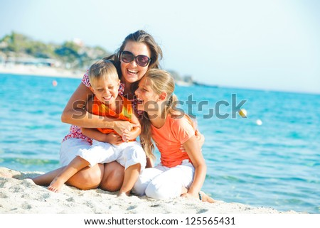 Photo of happy family laughing and looking at camera on the beach