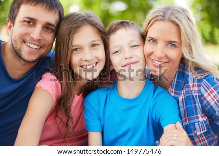 Photo of happy family of four looking at camera outdoors