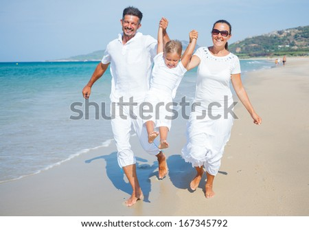 Photo of happy family running on the beach