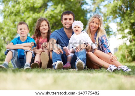 Photo of happy family sitting on grass during summer rest
