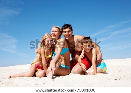 Photo of happy family sitting on sand on summer vacation