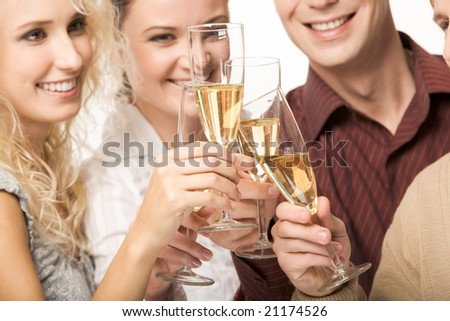 Photo of happy friends holding glasses full of champagne and smiling during party - stock photo