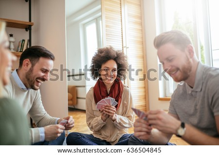 Photo of happy friends playing cards and hanging out together.