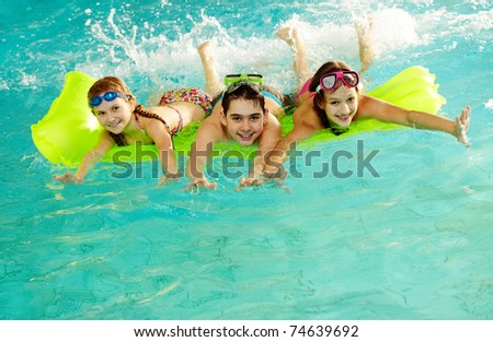 Photo of happy friends swimming in pool