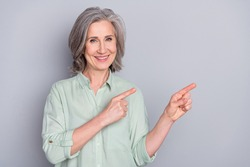 Photo of happy good mood lovely beautiful mature woman advertising product option isolated on grey color background